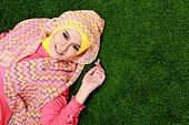 Young muslim girl wearing hijab lying on grass with copy space