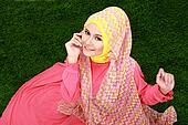 Portrait of young muslim girl wearing hijab sitting on grass and looking at camera