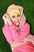 Portrait of young muslim girl wearing hijab lying on grass and looking at camera