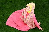 Young muslim girl wearing hijab sitting on grass